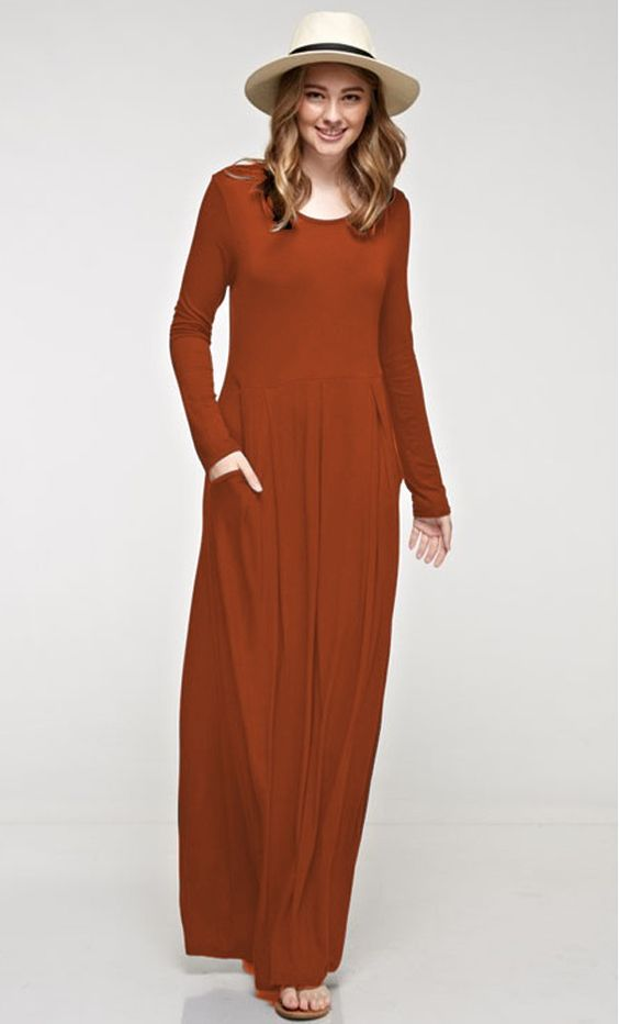 A modest womens long sleeve maxi dress with an elastic waist, side pockets and a slight pleated finish available in burgundy and rust S-L