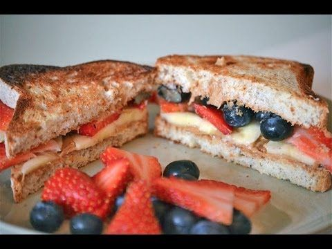 First put a layer of peanut butter on both slices of bread Top with banana and strawberry slices and blueberries.