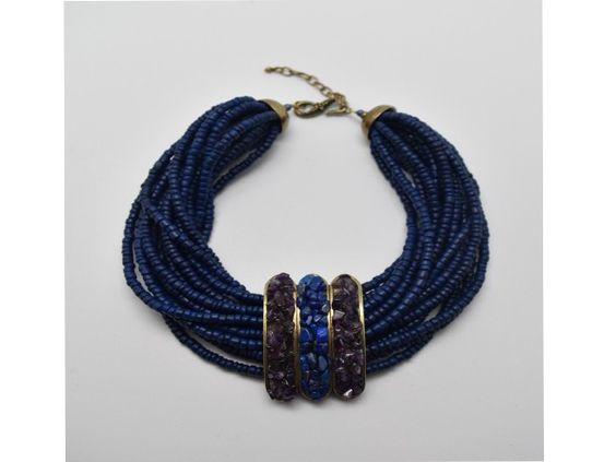 COLLIER KAYAPO Collier ethnique de 40 cm composé de 16 rangs de bois exotique bleu lapis retenus par une grande bague décorée de lapis lazuli et d'améthystes. Chainette de réglage de 7 cm, bague et fermoir finition bronze vieilli. Hauteur de la bague  7 cm Largeur totale de la bague  4.3 cm Poids  217 grammes