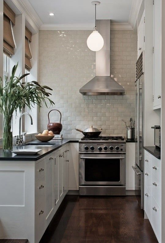 Kevin Dakan kitchen via Remodelista. Small white classic kitchen with glazed tile statement wall and dark counters. #smallkitchen #ushape #kitchendesign