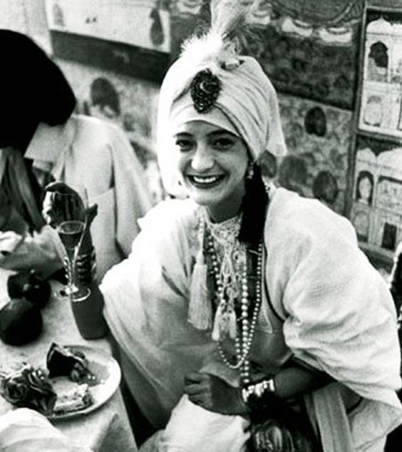 Loulou de la Falaise in a white feathered turban