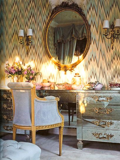 Flame patterned wallpaper, french mirrored vanity and gilt mirror topped with ostrich feathers. Ladylike and hip.