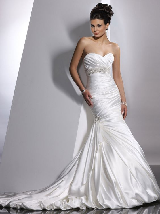 Sottero and Midgley - ADORAE, Fit and flare gown with sweetheart neckline and available with corset closure. Demir Stretch Satin provides sleek luster to this slender silhouette. Ruching envelopes the bodice and asymmetrically plummets below the waist, while the train pours into a gorgeous balloon hem.