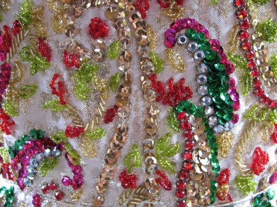 Detail of 1960's evening gown covered in diamantes and red, pink, green, lemon-lime, and gold sequins and beads