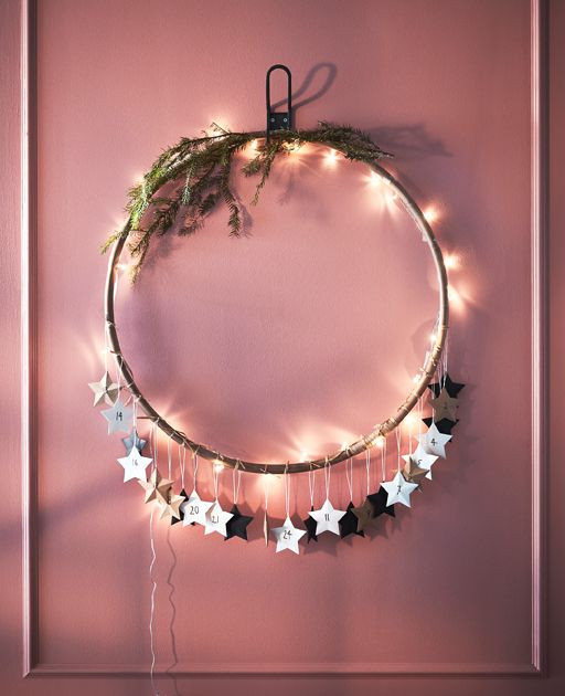 A hula hoop decorated with lights, greenery and paper stars hangs from a wall.