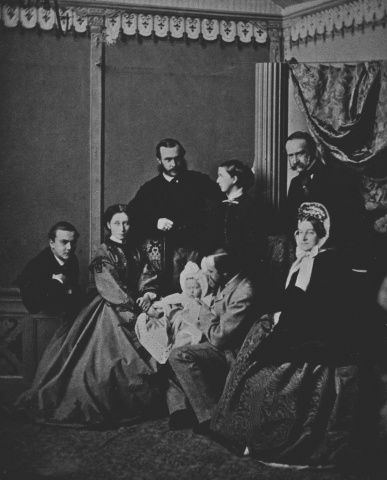 Dec 1863, Darmstadt; Left to r.: Prince William of Hesse; Alice, Pss Louis of Hesse; Prince Henry of Hesse (standing); Pss Anna of Hesse; P. Louis of Hesse holding his infant daughter Pss Victoria of Hesse on his lap; P. & Pss Charles of Hesse.