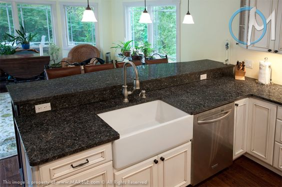Blue Pearl's consistent blue, black and silver specks provide solid contrast to the white farm sink and cabinets.