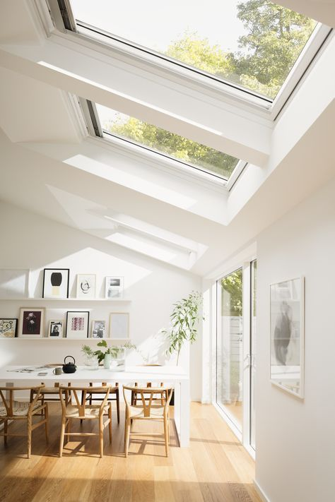 Bright Scandinavian dining room with roof windows and increased natural light.: