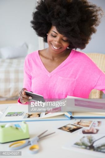 Mixed race woman putting photos in album