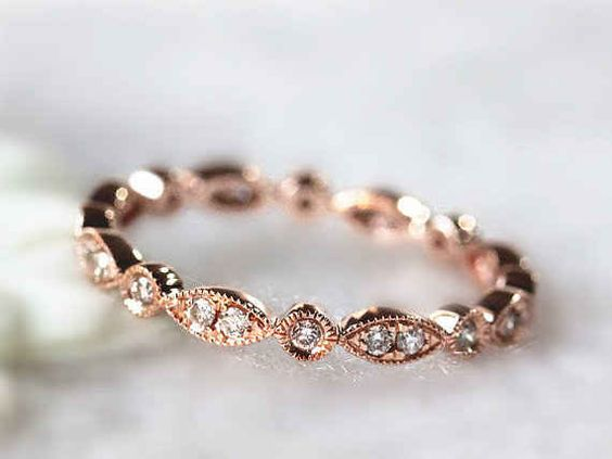This dainty daisy-chain diamond ring. Rose gold with a row of small diamonds around.