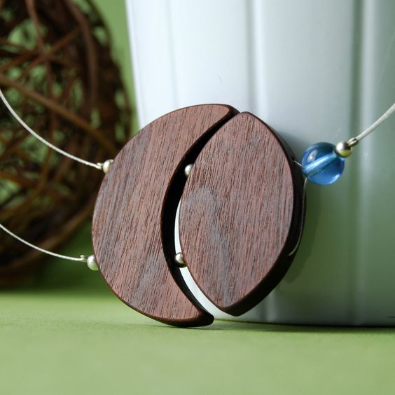 Celeste - asymetrical wood necklace with blue glass bead. $35.00, via Etsy.