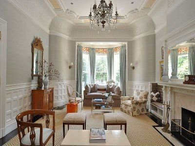 This Beacon Street living room has natural jute carpets, fireplace, high ceilings, patterned chair, wainscot and chandelier.