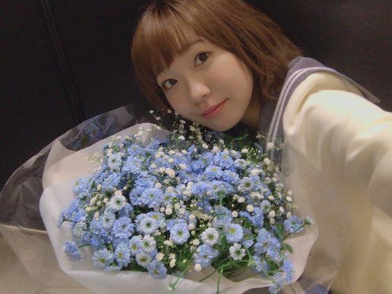 青い花の花束を持った斉藤朱夏