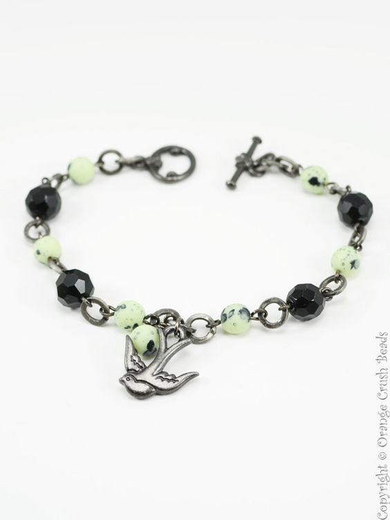 Bracelet 1436 -  	A cheerful black and mint beaded charm bracelet featuring a swooping swallow charm.