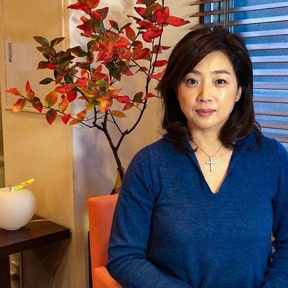 紅葉した木の前に座る紺色のトップスを着ている藤吉久美子の画像