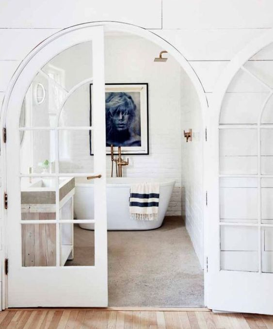Black and white bathroom with arched vintage French doors and white painted brick wall. A cool #bathroomdesign by #LeanneFord
