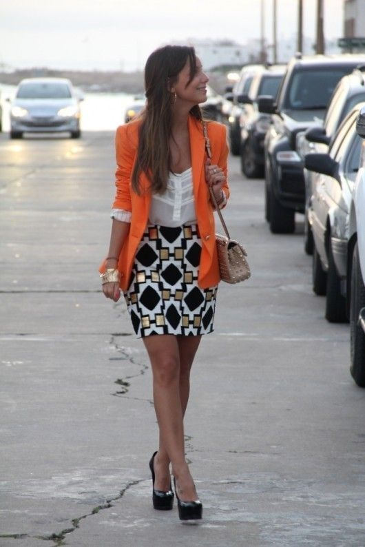 orange blazer, sheer top, patterned skirt, and platform pumps; cute, clean hairstyle