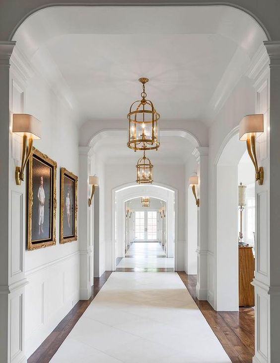 26 Interior Design Ideas With Wall Sconce: A Long Hallway Features Walls Clad In Wainscoting Lined