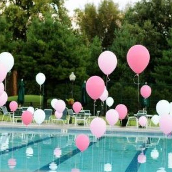 Helium filled balloons tied to weights in pool.  If you want to create the illusion of floating balloons use fishing line which is virtually invisible.