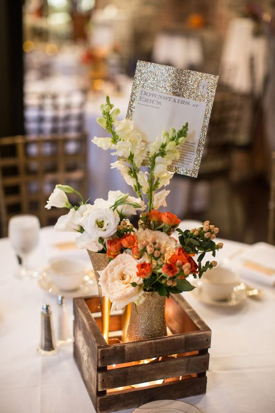 Gold glitter table names with candlelit floral centerpiece
