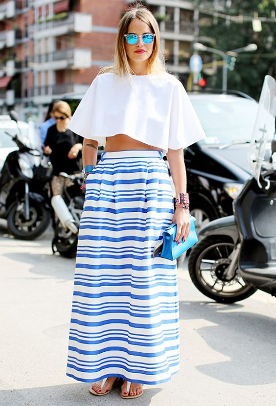A blue striped skirt is worn with a white crop top, white sandals ...