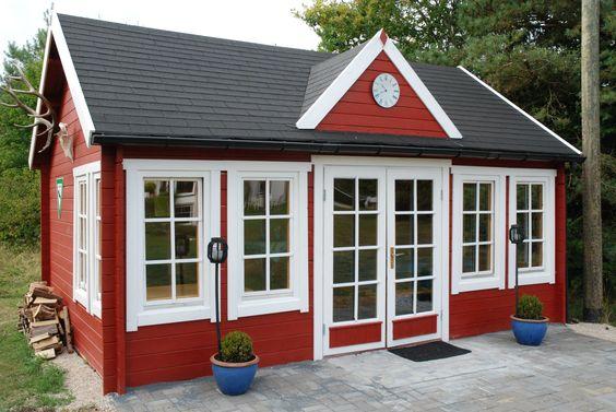 Schönes Clockhouse-Gartenhaus in Schwedenrot und Weiß mit Ziergiebel. Das traditionelle Flair wird durch ein Hirschgeweih und Brennholz unterstrichen.