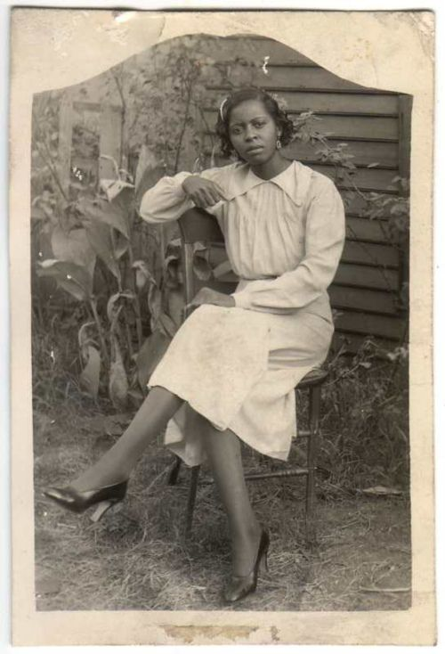 An African American women sitting in a chair with legs crossed. Name and location unknown. African American Vernacular Photography courtesy of Black History Album.