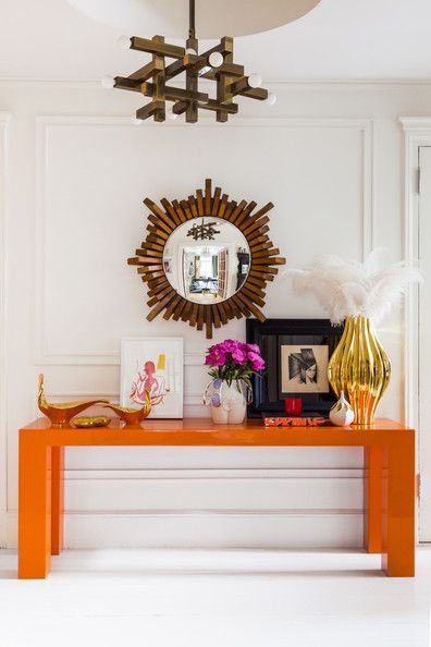 Simon Doonan - Below a mirror, an orange table topped with vases and other objets: