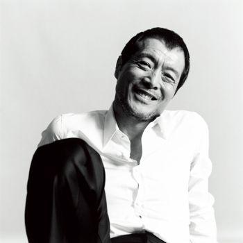 白いシャツを着て座って微笑んでいる矢沢永吉の画像