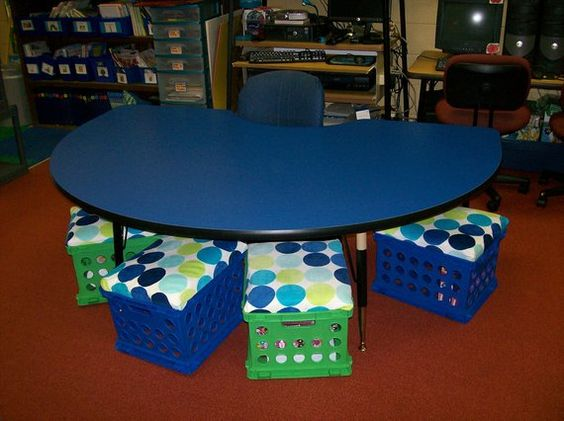 Use black crates with red seats and red crates with black seats. The seats double as storage. Look for the other picture using folders for worksheets and then store here? Do not like the rest of the classroom set up in this picture.