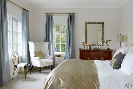 For a guest room, Hagan employed curtains of a Clarence House silk taffeta, a wing chair by Victoria Hagan Home Collection, a Gio Ponti brass chair, and bed linens by Frette; the carpet is by Stark.