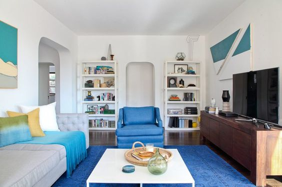 Pin for Later: The Recipe for a Relaxed Summer Home  Slim bookcases painted in a bright white add extra storage without adding visual weight. Source: Tessa Neustadt for Homepolish