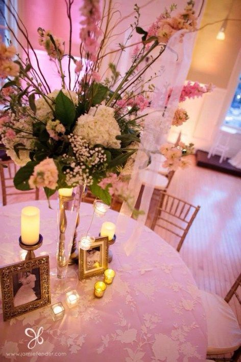 white lace tablecloths over pink underskirt, lots of gold candle holders, and beautiful floral centerpiece.