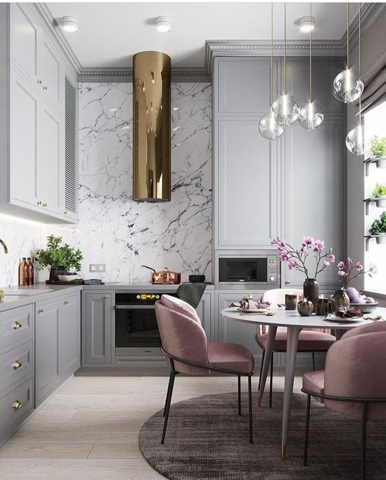Glamorous gray kitchen cabinets, marble backsplash, touches of gold and pink chairs