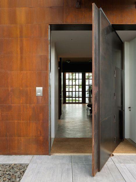 Puerta pivotante se ve muy minimalista dejando ver los detalles del material paisajismo - Architectuur staal corten ...