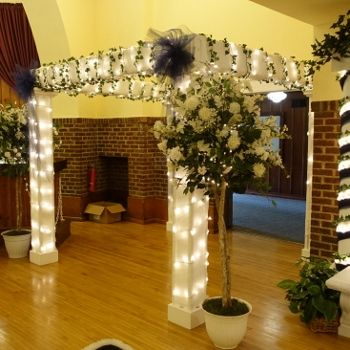 """Amazing four-poster """"chuppah"""" can be decorated to match any color scheme. Here it makes a """"grand entrance"""" and is paired with two of our """"exploding"""" white topiaries! @ Chandelier Ballroom, Hartford WI"""