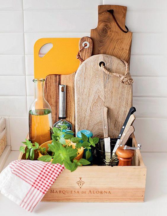 Tábuas, facas, ralador... Tem espaço até para um vasinho com ervas na caixa de vinho feita de madeira. Tábuas e saleiro e pimenteiro azuis Utilplast, ralador e moedor M. Dragonetti, pano de copa Tok & Stok (Foto: Elisa Correa/Editora Globo):
