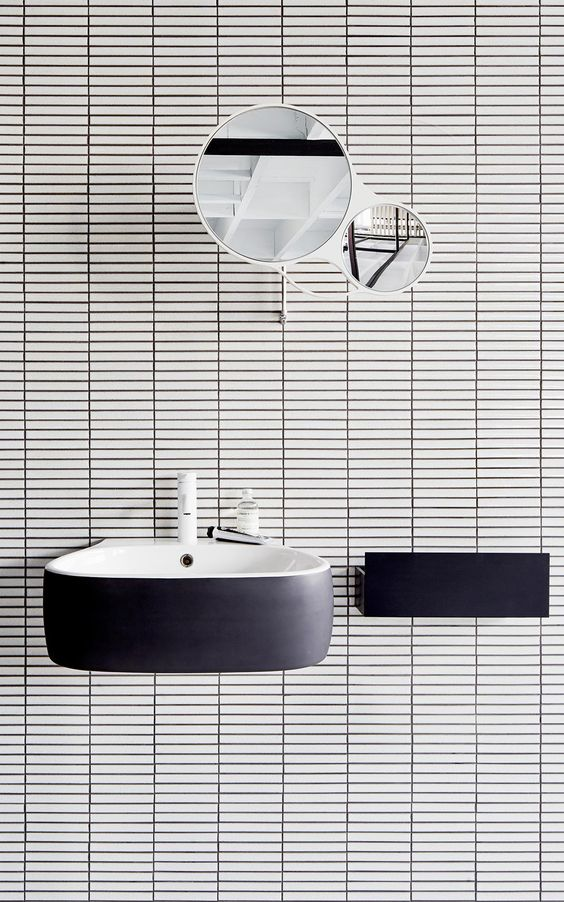 floating sink + white tile + black grout + round mirror: