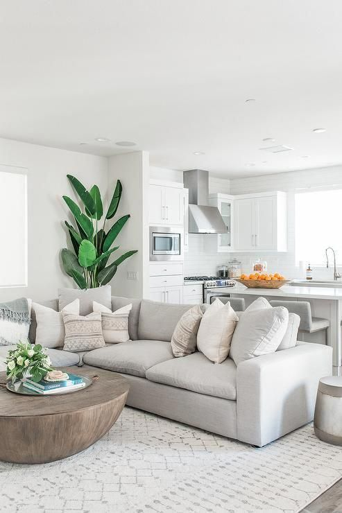 Stone Gray Low Sectional Sofa Paired With A Round Wood Coffee Table Atop A Cream Atop White Living Room Decor Modern White Living Room Living Room White
