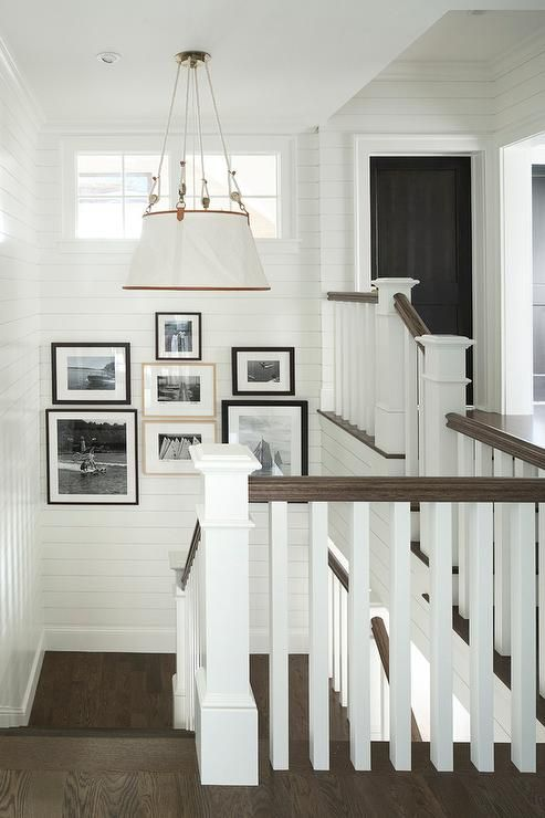 Cottage shiplap staircase surrounds shiplap walls showcasing a black and white photo gallery under a small window.