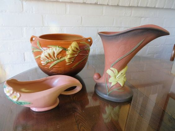 """3 pieces of Roseville pottery including 2 handled pot with Freesia marked 669-6"""", vase with lily marked 204-8"""", and aladdin lamp with dogwood."""