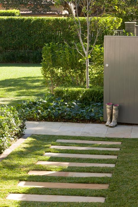 Wide sandstone (? or concrete based) slabs act as a walkway through the lawn leading to a focal point of gumboots.