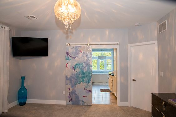 The divider between the master bedroom and bath, is a sliding door that was hand painted to feature a modern artwork.