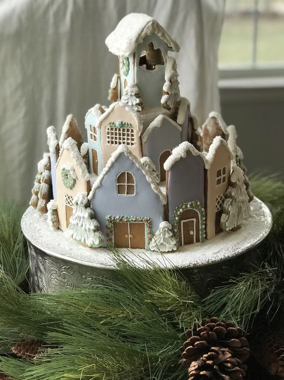 Gingerbread Christmas village with pastel houses and flocked snowy trees. DIY gingerbread house! Decorated cookies