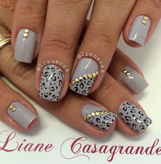Leopard print winter nail art design. Paint on leopard prints on your gray nail polish and add gold embellishments on top for accent.: