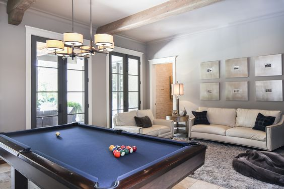 "For the game room, Stacy chose low-maintenance materials like a porcelain tile floor and leather seating that would stand up to ""dripping kids"" coming in and out through the French doors that open onto the pool and porch."