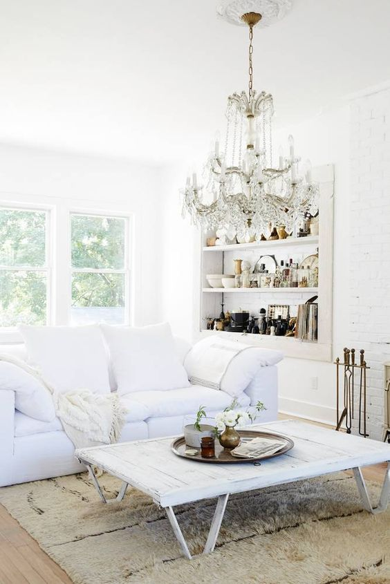 A white living room with crystal chandelier and vintage treasures by #LeanneFord. #livingroomdecor #crystalchandelier #allwhitedecor