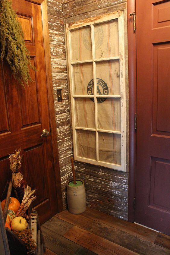 Primitive barn wood wall in my foyer..Took an old window put a feed sack behind it to make it look like a real window..butter churn on floor.