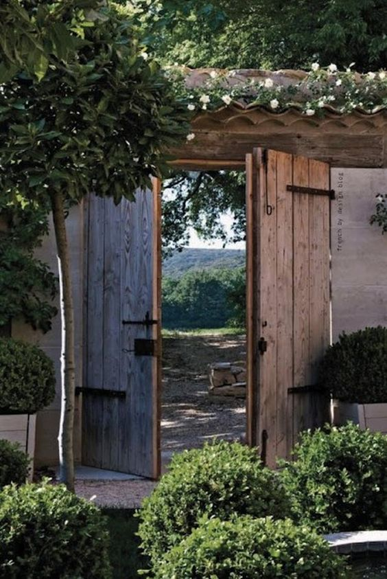 Garden gate ideas and garden inspiration: rustic planked garden gate doors to a beautiful lush garden with French Country style. #gardengate #frenchcountry #rustic #gardenideas #Provence