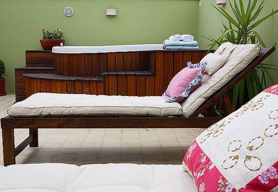 Terraço com chaises e almofadas cria um canto de relaxamento de uma casa. Com deque de madeira, a banheira completa o espaço. A parede recebeu a cor verde clara